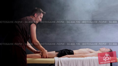 Massage session in dark studio - massagist massaging the man's knees. Стоковое видео, видеограф Константин Шишкин / Фотобанк Лори