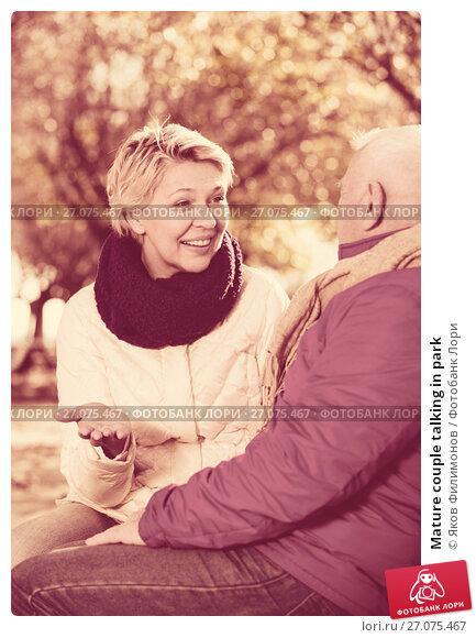 Mature couple talking in park, фото № 27075467, снято 17 октября 2017 г. (c) Яков Филимонов / Фотобанк Лори