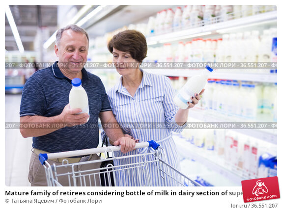 Mature family of retirees considering bottle of milk in dairy section of supermarket. Стоковое фото, фотограф Татьяна Яцевич / Фотобанк Лори