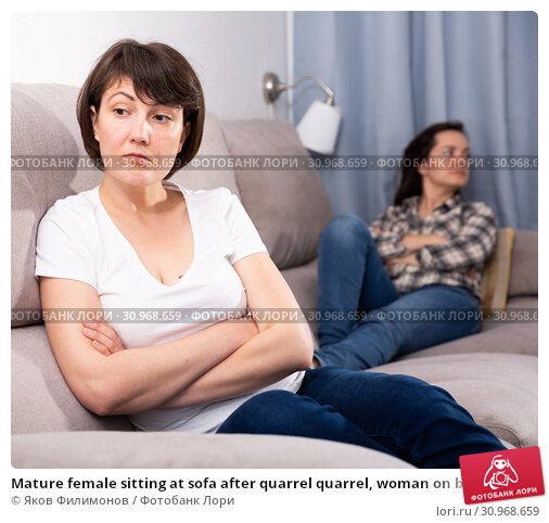 Купить «Mature female sitting at sofa after quarrel quarrel, woman on background», фото № 30968659, снято 22 июля 2019 г. (c) Яков Филимонов / Фотобанк Лори