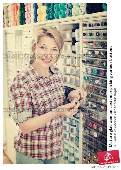 Купить «Mature glad woman customer picking various buttons», фото № 23499615, снято 22 мая 2019 г. (c) Яков Филимонов / Фотобанк Лори