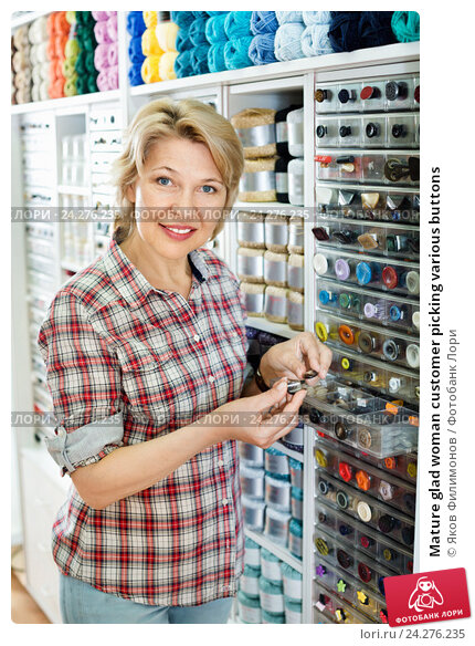Купить «Mature glad woman customer picking various buttons», фото № 24276235, снято 20 мая 2019 г. (c) Яков Филимонов / Фотобанк Лори
