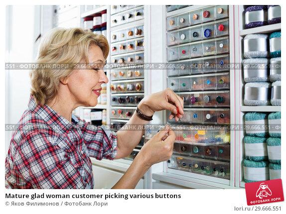 Купить «Mature glad woman customer picking various buttons», фото № 29666551, снято 23 мая 2019 г. (c) Яков Филимонов / Фотобанк Лори