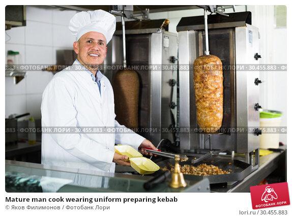 Mature man cook wearing uniform preparing kebab. Стоковое фото, фотограф Яков Филимонов / Фотобанк Лори