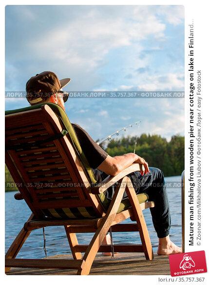 Mature man fishing from wooden pier near cottage on lake in Finland... Стоковое фото, фотограф Zoonar.com/Mikhailova Liubov / easy Fotostock / Фотобанк Лори