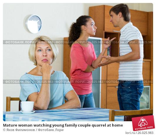 Mature woman watching young family couple quarrel at home, фото № 26025983, снято 27 апреля 2017 г. (c) Яков Филимонов / Фотобанк Лори