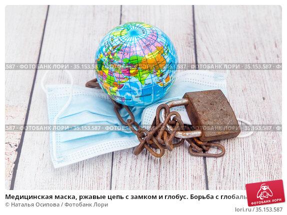 Медицинская маска, ржавые цепь с замком и глобус. Борьба с глобальной эпидемией. Стоковое фото, фотограф Наталья Осипова / Фотобанк Лори