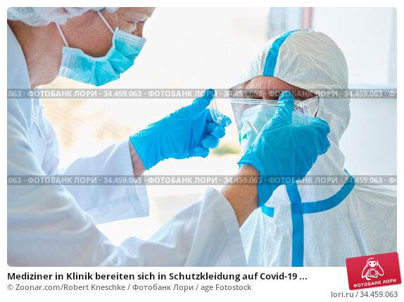 Mediziner in Klinik bereiten sich in Schutzkleidung auf Covid-19 ... Стоковое фото, фотограф Zoonar.com/Robert Kneschke / age Fotostock / Фотобанк Лори