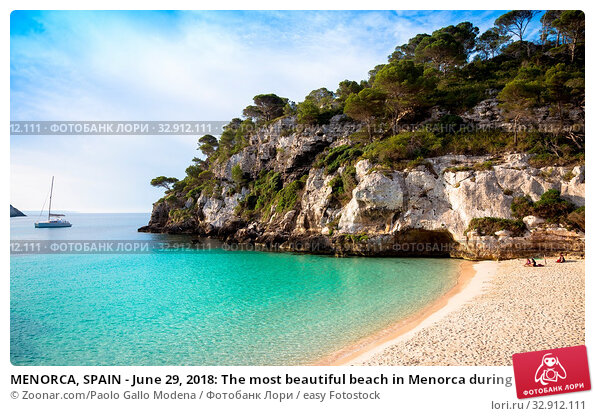MENORCA, SPAIN - June 29, 2018: The most beautiful beach in Menorca during first hours of the day (07:00), summer season. Стоковое фото, фотограф Zoonar.com/Paolo Gallo Modena / easy Fotostock / Фотобанк Лори