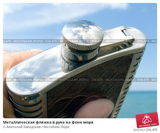 Металлическая фляжка в руке на фоне моря, фото № 316475, снято 27 мая 2006 г. (c) Анатолий Заводсков / Фотобанк Лори