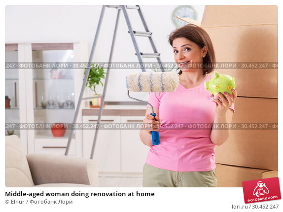 Middle-aged woman doing renovation at home. Стоковое фото, фотограф Elnur / Фотобанк Лори