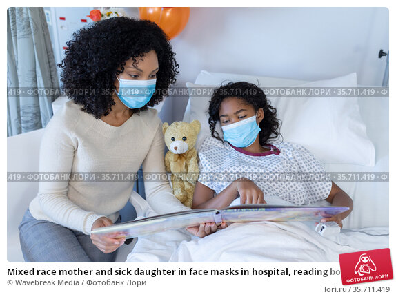 Mixed race mother and sick daughter in face masks in hospital, reading book with teddy bear. Стоковое фото, агентство Wavebreak Media / Фотобанк Лори