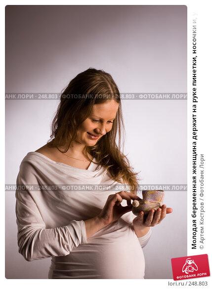 Купить «Молодая беременная женщина держит на руке пинетки, носочки и, улыбаясь, их разглядывает», фото № 248803, снято 4 апреля 2008 г. (c) Артем Костров / Фотобанк Лори