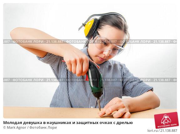 Купить «Молодая девушка в наушниках и защитных очках с дрелью», фото № 21138887, снято 20 января 2016 г. (c) Mark Agnor / Фотобанк Лори