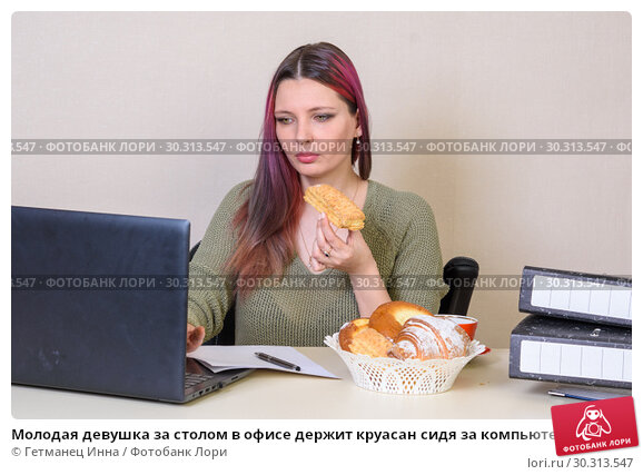 Купить «Молодая девушка за столом в офисе держит круасан сидя за компьютером», фото № 30313547, снято 14 марта 2019 г. (c) Гетманец Инна / Фотобанк Лори