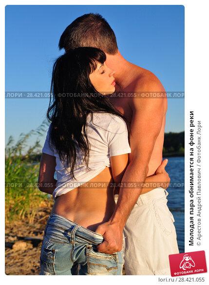 Купить «Молодая пара обнимается на фоне реки», фото № 28421055, снято 20 сентября 2015 г. (c) Арестов Андрей Павлович / Фотобанк Лори