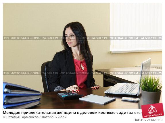 Купить «Молодая привлекательная женщина в деловом костюме сидит за столом в офисе», фото № 24668119, снято 6 мая 2016 г. (c) Наталья Гармашева / Фотобанк Лори
