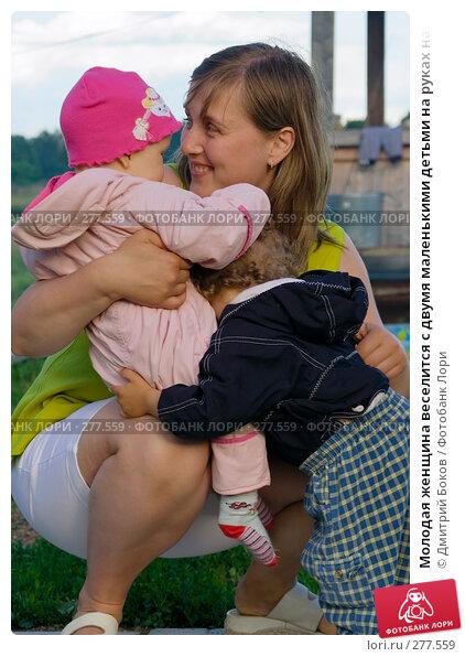 Молодая женщина веселится с двумя маленькими детьми на руках на фоне деревенского двора, фото № 277559, снято 24 июня 2006 г. (c) Дмитрий Боков / Фотобанк Лори