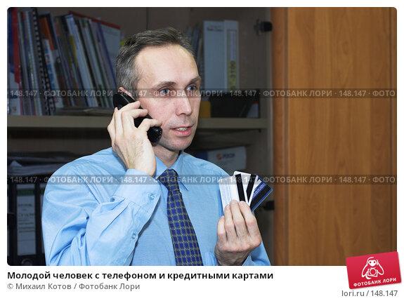 Молодой человек с телефоном и кредитными картами, фото № 148147, снято 11 декабря 2016 г. (c) Михаил Котов / Фотобанк Лори