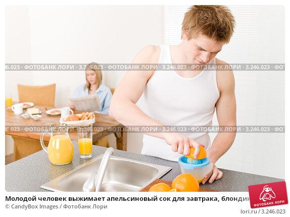 Купить «Молодой человек выжимает апельсиновый сок для завтрака, блондинка на заднем плане», фото № 3246023, снято 16 апреля 2011 г. (c) CandyBox Images / Фотобанк Лори