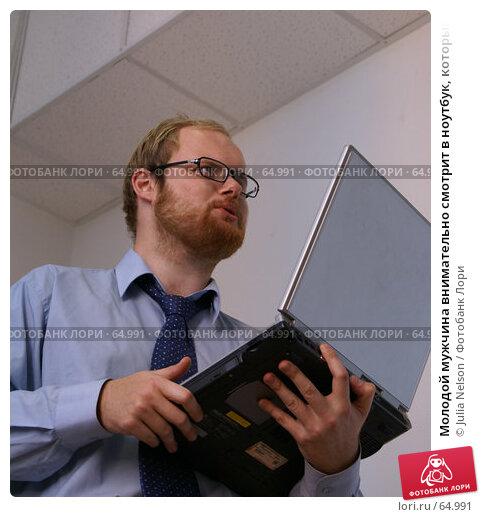 Молодой мужчина внимательно смотрит в ноутбук, который держит в руках, фото № 64991, снято 22 июля 2007 г. (c) Julia Nelson / Фотобанк Лори