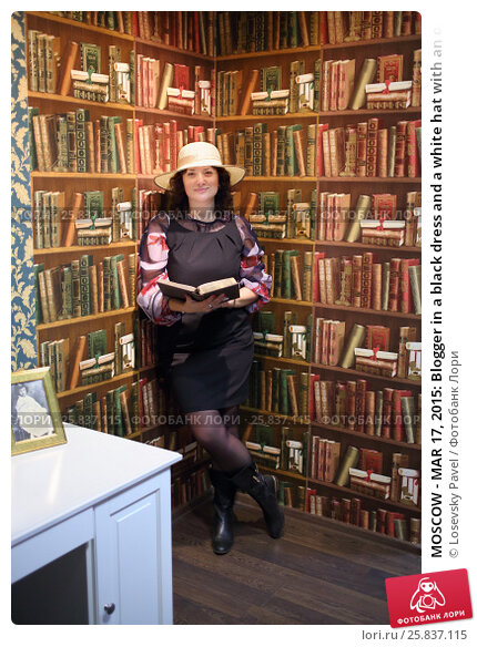 Купить «MOSCOW - MAR 17, 2015: Blogger in a black dress and a white hat with an open book stands near a wall with painted shelves and books in the quest Funlock for bloggers», фото № 25837115, снято 17 марта 2015 г. (c) Losevsky Pavel / Фотобанк Лори