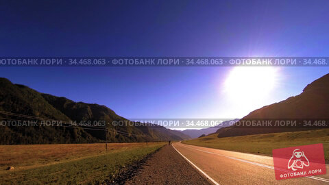 Mountain road timelapse at the summer or autumn sunset sunrise time. Wild nature and rural field. Стоковое видео, видеограф Александр Маркин / Фотобанк Лори