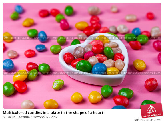 Multicolored candies in a plate in the shape of a heart. Стоковое фото, фотограф Елена Блохина / Фотобанк Лори