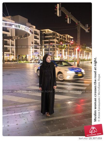 Купить «Muslim woman crosses the road at night.», фото № 28307059, снято 25 марта 2018 г. (c) Женя Канашкин / Фотобанк Лори