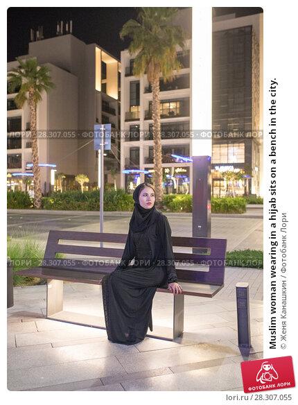 Купить «Muslim woman wearing in a hijab sits on a bench in the city.», фото № 28307055, снято 25 марта 2018 г. (c) Женя Канашкин / Фотобанк Лори