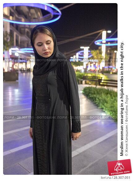 Купить «Muslim woman wearing in a hijab walks in the night city.», фото № 28307051, снято 25 марта 2018 г. (c) Женя Канашкин / Фотобанк Лори