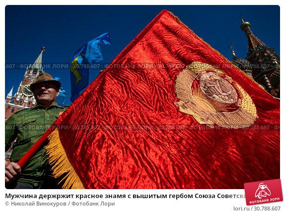 Купить «Мужчина держржит красное знамя с вышитым гербом Союза Советских Социалистических Республик на Красной площади в центре города Москвы, Россия», фото № 30788607, снято 19 мая 2019 г. (c) Николай Винокуров / Фотобанк Лори