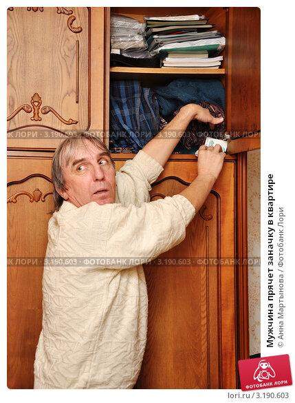 Купить «Мужчина прячет заначку в квартире», эксклюзивное фото № 3190603, снято 23 декабря 2011 г. (c) Анна Мартынова / Фотобанк Лори