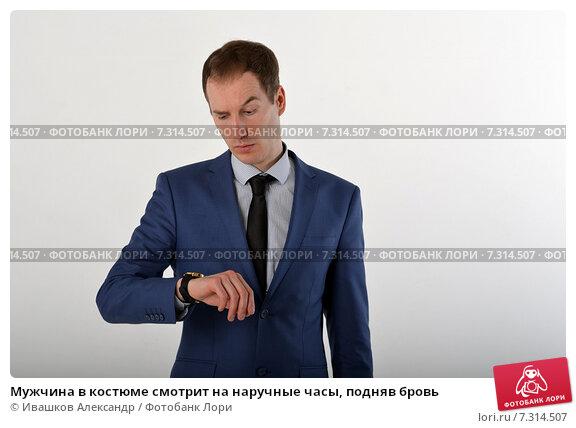 Купить «Мужчина в костюме смотрит на наручные часы, подняв бровь», фото № 7314507, снято 19 апреля 2015 г. (c) Ивашков Александр / Фотобанк Лори