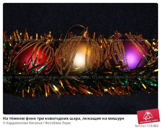 Купить «На тёмном фоне три новогодних шара, лежащие на мишуре», фото № 113463, снято 6 ноября 2007 г. (c) Кардаполова Наталья / Фотобанк Лори