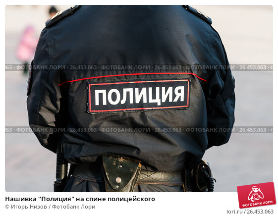 """Купить «Нашивка """"Полиция"""" на спине полицейского», эксклюзивное фото № 26453063, снято 22 мая 2017 г. (c) Игорь Низов / Фотобанк Лори"""
