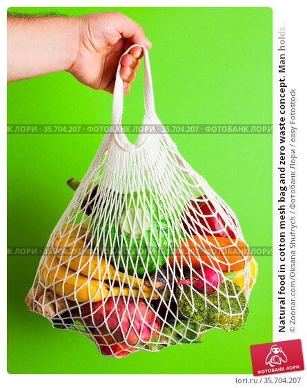 Natural food in cotton mesh bag and zero waste concept. Man holds... Стоковое фото, фотограф Zoonar.com/Oksana Shufrych / easy Fotostock / Фотобанк Лори