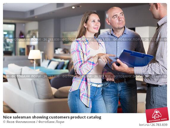 Nice salesman showing customers product catalog, фото № 26783839, снято 16 мая 2017 г. (c) Яков Филимонов / Фотобанк Лори