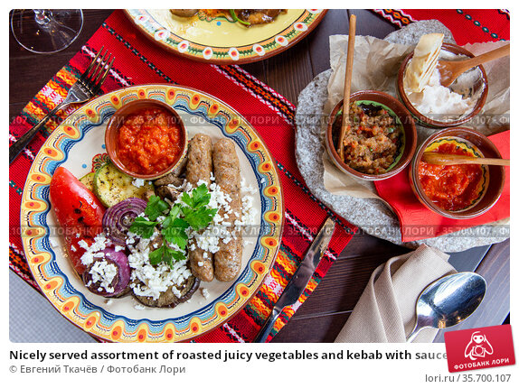 Nicely served assortment of roasted juicy vegetables and kebab with sauce and cheese feta in restaurant. Стоковое фото, фотограф Евгений Ткачёв / Фотобанк Лори