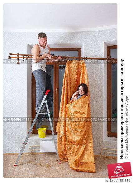 Новоселы примеряют новые шторы к  карнизу, фото № 155339, снято 5 декабря 2007 г. (c) Ирина Мойсеева / Фотобанк Лори