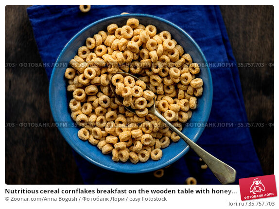 Nutritious cereal cornflakes breakfast on the wooden table with honey... Стоковое фото, фотограф Zoonar.com/Anna Bogush / easy Fotostock / Фотобанк Лори
