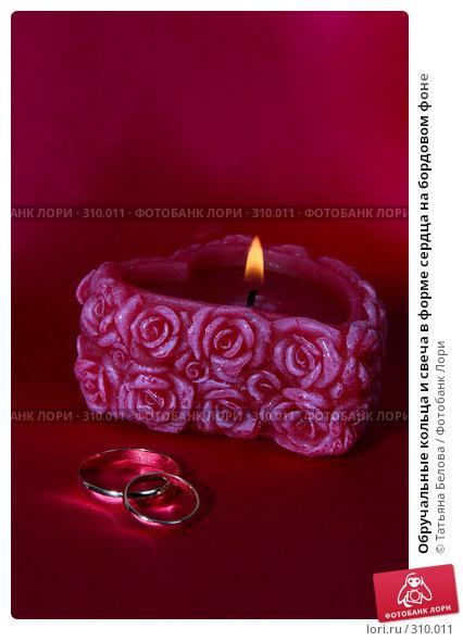 Обручальные кольца и свеча в форме сердца на бордовом фоне, фото № 310011, снято 13 мая 2008 г. (c) Татьяна Белова / Фотобанк Лори