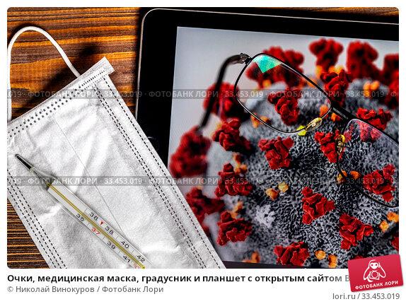 Купить «Очки, медицинская маска, градусник и планшет с открытым сайтом Википедии на странице с информацией об эпидемии коронавируса COVID-19 и изображением вируса под микроскопом», фото № 33453019, снято 30 марта 2020 г. (c) Николай Винокуров / Фотобанк Лори