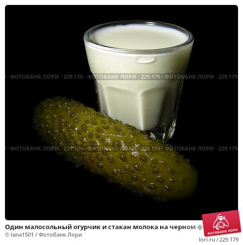 Один малосольный огурчик и стакан молока на черном фоне, эксклюзивное фото № 229179, снято 21 марта 2008 г. (c) lana1501 / Фотобанк Лори