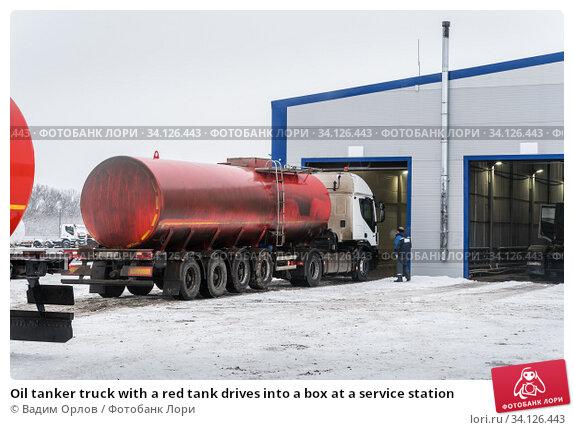 Купить «Oil tanker truck with a red tank drives into a box at a service station», фото № 34126443, снято 18 декабря 2019 г. (c) Вадим Орлов / Фотобанк Лори
