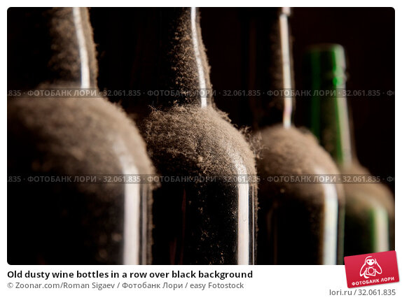 Old dusty wine bottles in a row over black background. Стоковое фото, фотограф Zoonar.com/Roman Sigaev / easy Fotostock / Фотобанк Лори