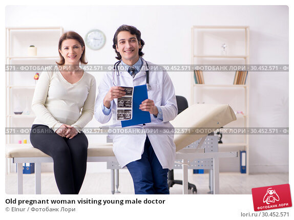 Old pregnant woman visiting young male doctor. Стоковое фото, фотограф Elnur / Фотобанк Лори