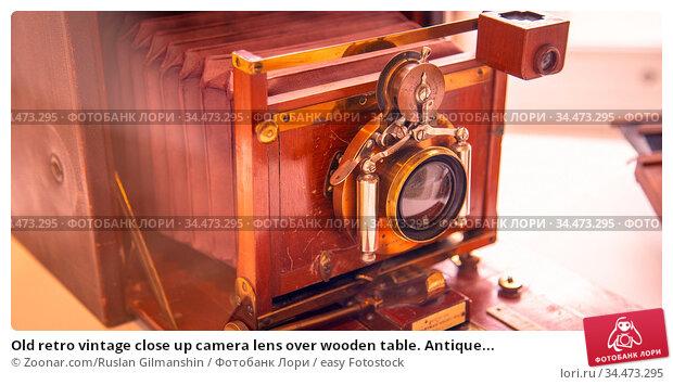 Old retro vintage close up camera lens over wooden table. Antique... Стоковое фото, фотограф Zoonar.com/Ruslan Gilmanshin / easy Fotostock / Фотобанк Лори