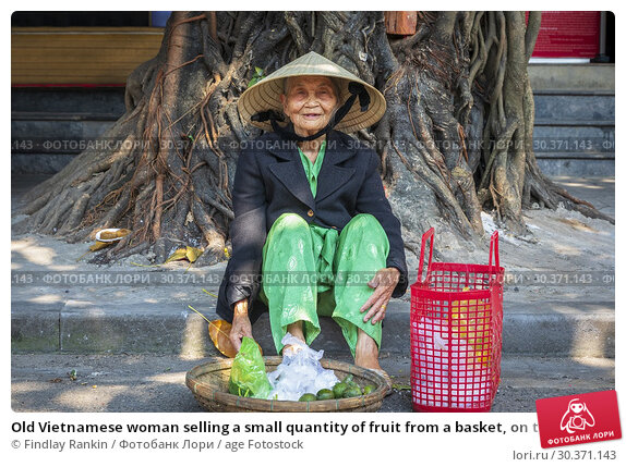 Купить «Old Vietnamese woman selling a small quantity of fruit from a basket, on the street in the old fruit market, Hoi An, Quang Nam Provence, Vietnam, Asia. Hoi An is also known as Fai-fo and Faifoo.», фото № 30371143, снято 7 февраля 2019 г. (c) age Fotostock / Фотобанк Лори