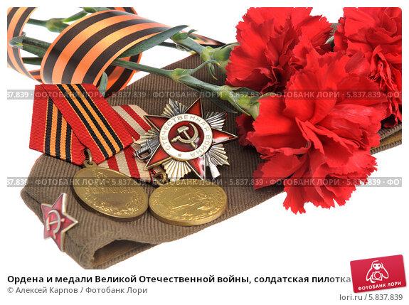 Ордена и медали Великой Отечественной войны, солдатская пилотка и красные гвоздики, перевязанные Георгиевской лентой. Стоковое фото, фотограф Алексей Карпов / Фотобанк Лори